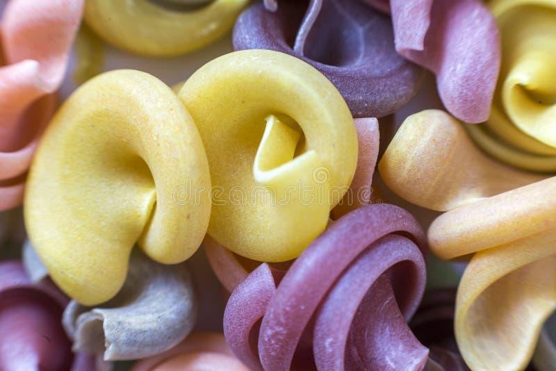 Primer del fondo abstracto de las pastas coloridas crudas secas crudas de los tallarines Ingrediente popular de la cocina tradici fotos de archivo