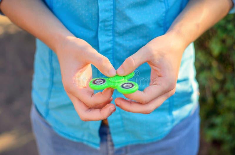 Primer del hilandero de moda del verde de la persona agitada en la mano de un m joven fotos de archivo libres de regalías