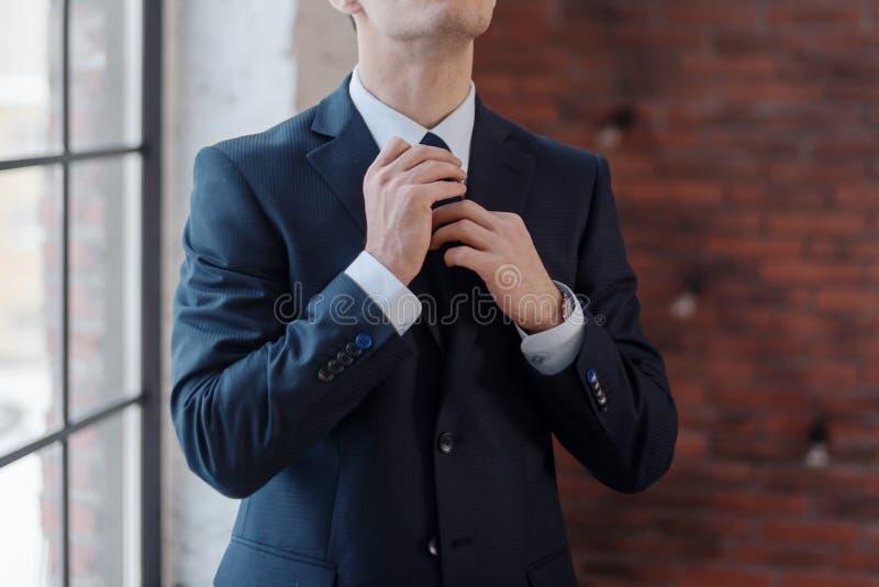 Primer del hombre de negocios que ajusta su corbata que se coloca en oficina imagenes de archivo