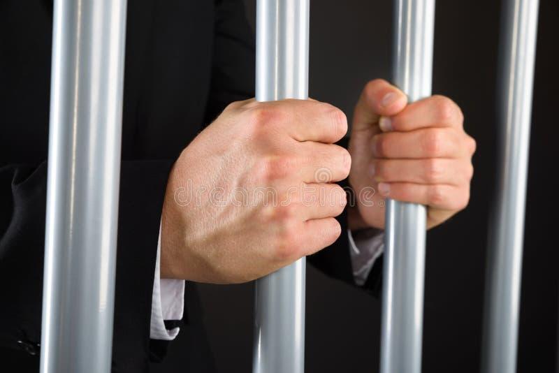 Primer del hombre de negocios que sostiene barras en cárcel imagen de archivo