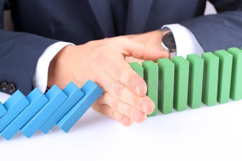 Primer del hombre de negocios Stopping The Effect del dominó con la mano imagenes de archivo