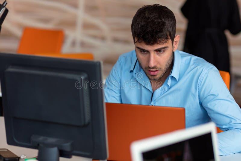 Primer del hombre joven chocado que trabaja en el ordenador portátil foto de archivo libre de regalías