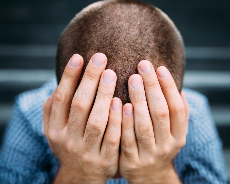 Primer del hombre joven desesperado que cubre su cara con las manos imagenes de archivo