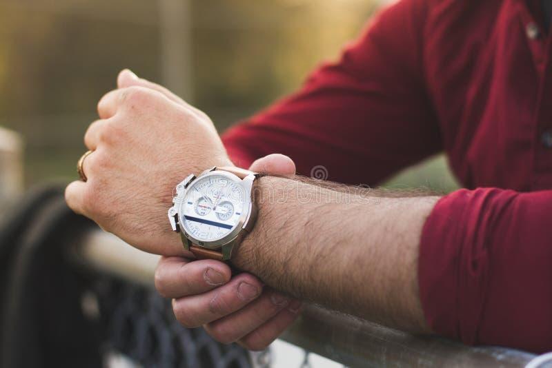 Primer del hombre joven en ropa informal que comprueba el reloj de lujo fotos de archivo libres de regalías