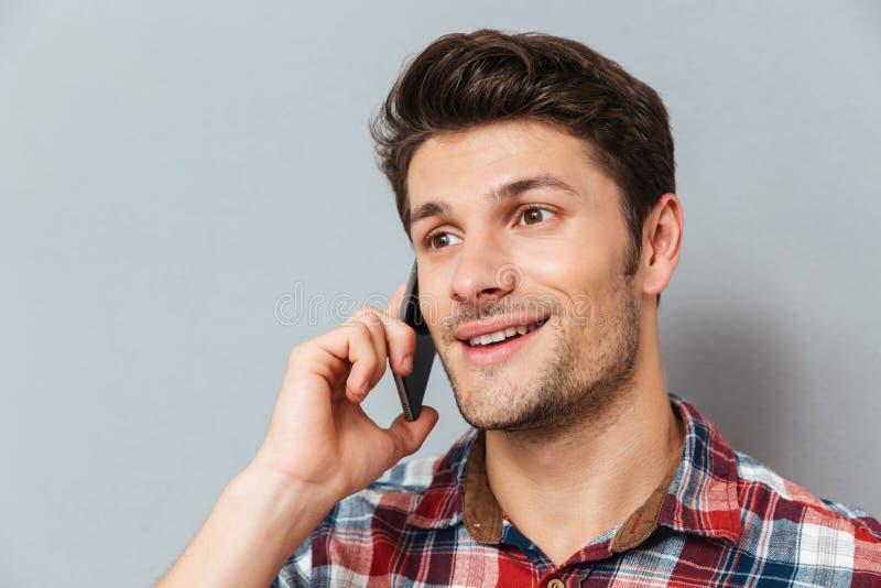 Primer del hombre joven feliz que habla en el teléfono celular imágenes de archivo libres de regalías