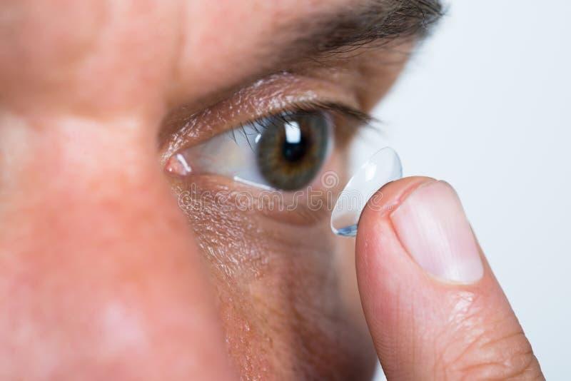 Primer del hombre que pone la lente de contacto en ojo foto de archivo