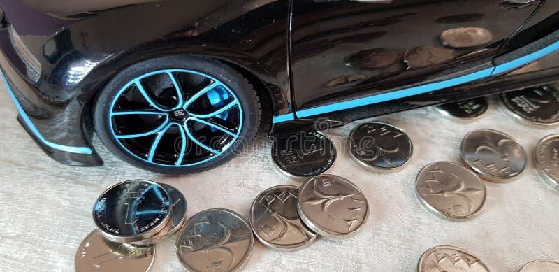 Primer del juguete negro del metal de Bugatti Chiron con las ruedas azules que se colocan en grupo de monedas israelíes de un she foto de archivo libre de regalías