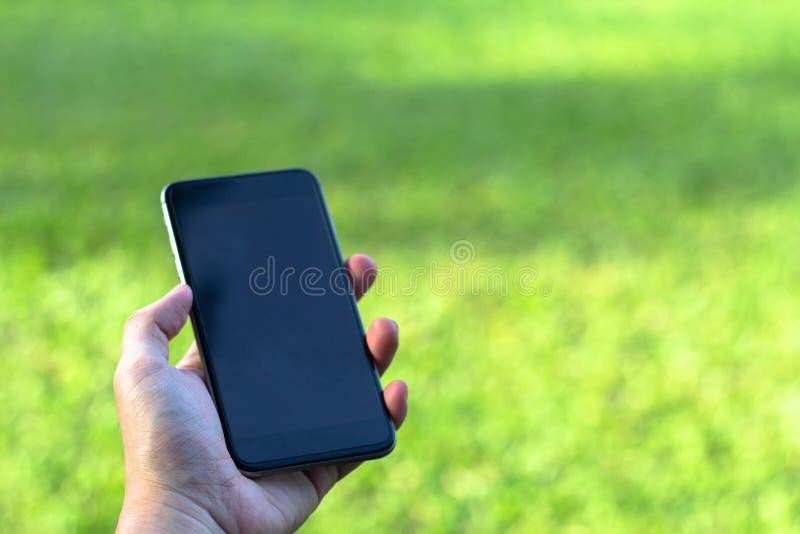 Primer del man& x27; mano de s que sostiene y que usa el teléfono elegante con s en blanco fotos de archivo
