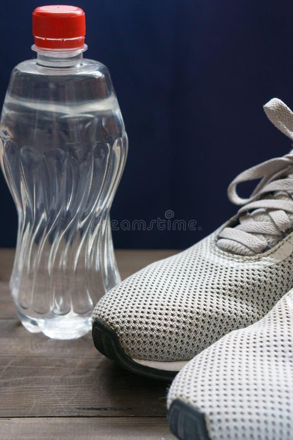 Primer del man& x27; zapatillas de deporte de s con la botella de agua imagen de archivo