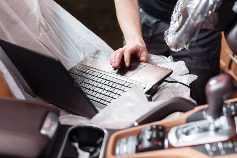 Primer del mecánico que usa el ordenador portátil digital mientras que examina el motor de coche en garaje conecte el conector de fotos de archivo