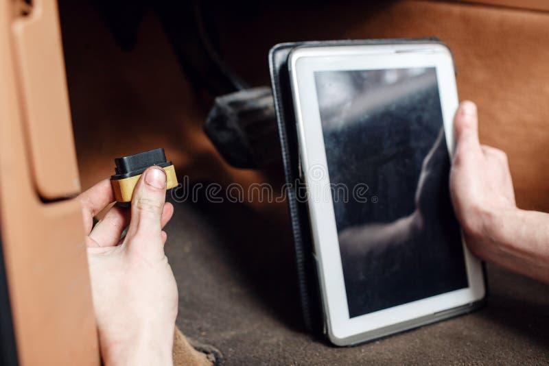 Primer del mecánico que usa el ordenador portátil digital mientras que examina el motor de coche en garaje conecte el conector de imágenes de archivo libres de regalías