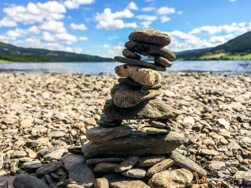 Primer del mojón de piedra en un Pebble Beach con las montañas y el lago en el fondo imagen de archivo libre de regalías