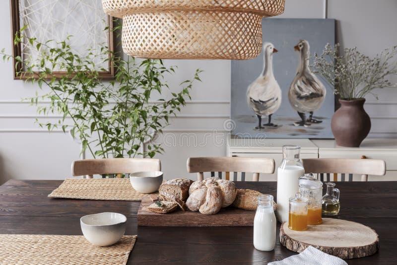 Primer del pan fresco y de la leche en una tabla en un interior acogedor del comedor en un campo fotografía de archivo