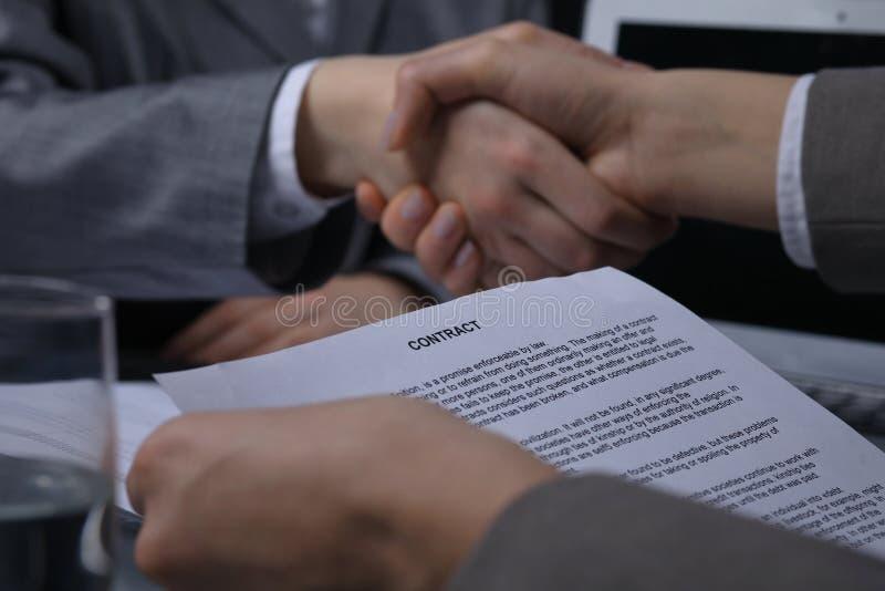 Primer del papel del contrato con el apretón de manos del negocio en el fondo Concepto acertado de la negociación o de la reunión foto de archivo libre de regalías