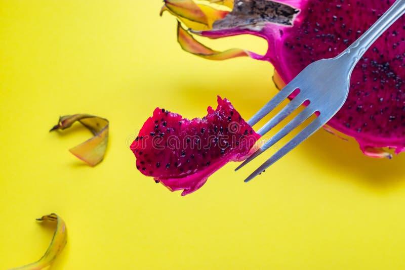 Primer del pedazo del pitaya mordido, fruta del dragón en la bifurcación, fondo amarillo imagenes de archivo