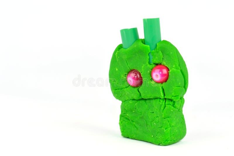Primer del pequeño monstruo verde hecho de la arcilla de modelado aislada en el fondo blanco imagenes de archivo