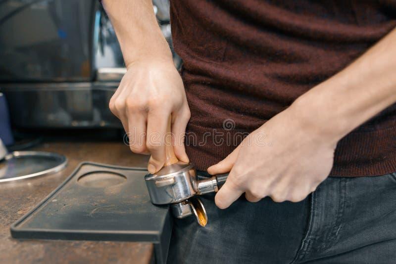 Primer del proceso de fabricación del café, manos del barista usando una máquina del café foto de archivo libre de regalías