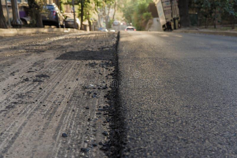 Primer del proceso de la reparación del camino que pavimenta el uso del asfalto del camino Obras por carretera en la colocación d fotografía de archivo