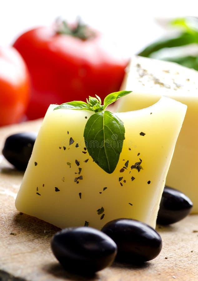 Primer del queso de cabra, de aceitunas, del tomate fresco, de la albahaca y de las especias en tabla de cortar de madera imagen de archivo