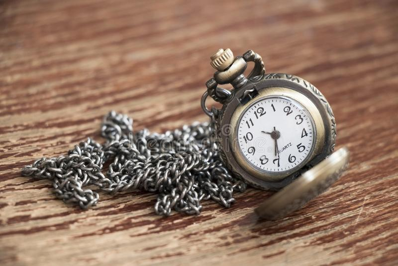 Primer del reloj abierto del bolsillo del vintage del metal con la cadena en o marrón fotografía de archivo
