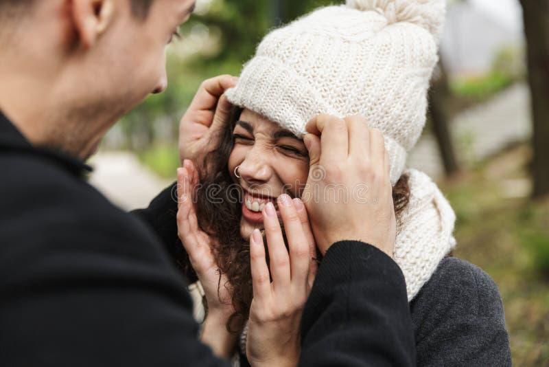Primer del retrato del hombre alegre y de la mujer 20s de la gente que abrazan y que sonríen, mientras que camina a través de par fotos de archivo libres de regalías