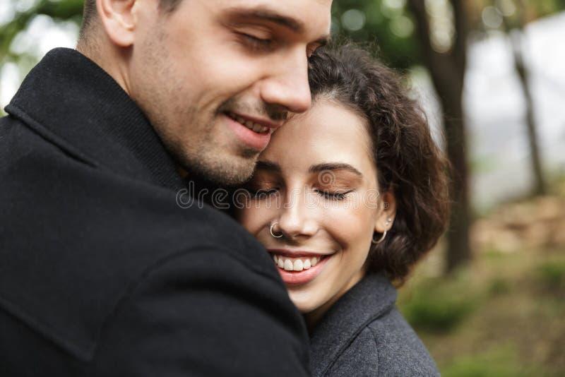 Primer del retrato del hombre feliz y de la mujer 20s de la gente que abrazan, mientras que camina a través de parque verde imágenes de archivo libres de regalías