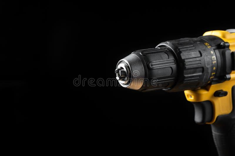 Primer del taladro eléctrico en un fondo negro con madera y taladros Herramientas el?ctricas Destornillador de la batería de la m fotos de archivo libres de regalías