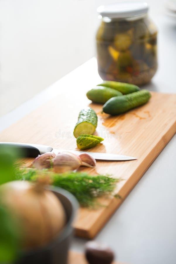 Primer del tarro fresco de los pepinos, del eneldo, del ajo, de la cebolla y de la conserva en vinagre foto de archivo