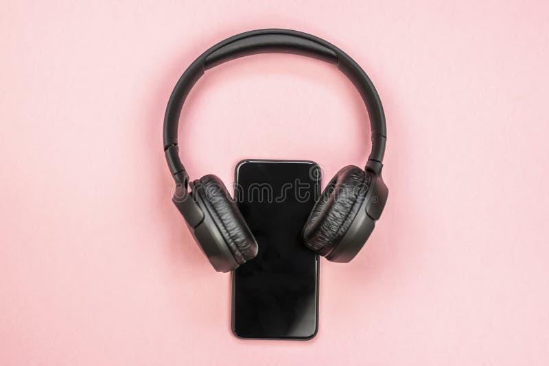 Primer del tel?fono elegante con los auriculares en un fondo rosado imagen de archivo