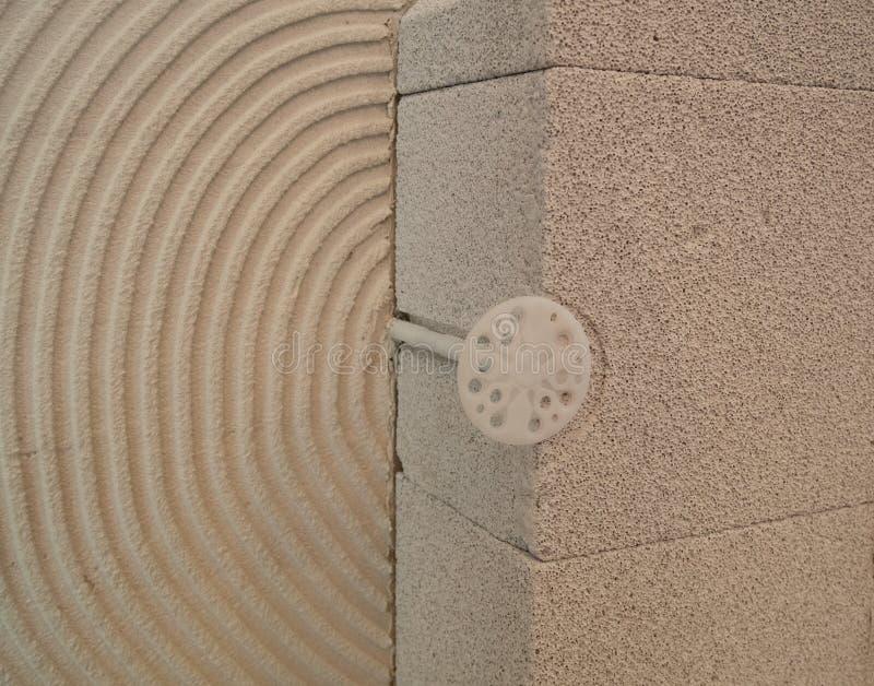 Primer del tenedor plástico del clavo en pared de la casa en un corte en el emplazamiento de la obra con los bloques concretos d fotos de archivo