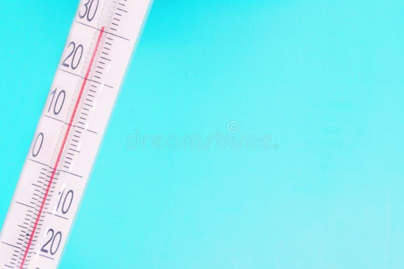 Primer del termómetro en un fondo azul, de alta temperatura en la escala del termómetro, equipo meteorológico, temperatura del ai imagenes de archivo