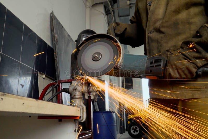 Primer del trabajador que usa un metal de los cortes de la amoladora en un taller foto de archivo libre de regalías