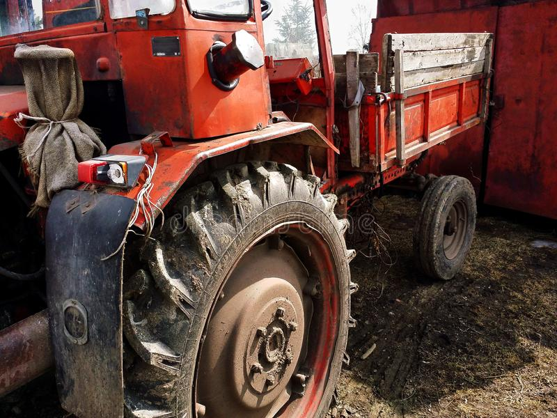 Primer del tractor rojo oscuro descuidado viejo con las ruedas sucias de goma imagen de archivo