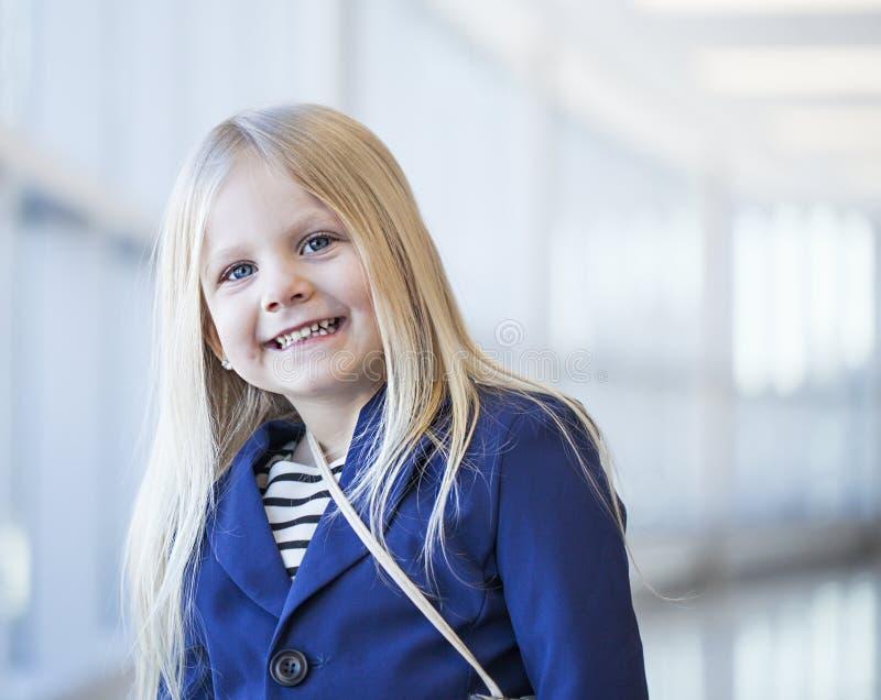 Primer del vestido que lleva de la niña feliz y de la chaqueta azul fotografía de archivo libre de regalías