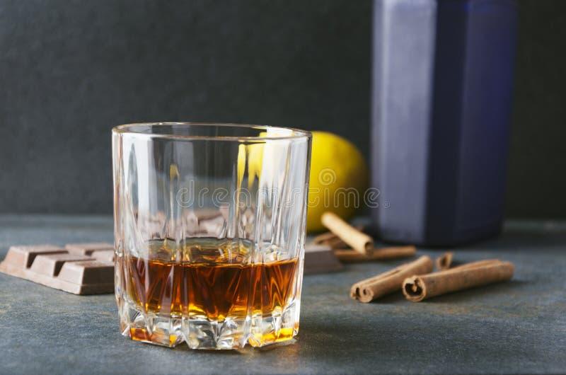 Primer del vidrio del brandy, del limón, del chocolate, del canela y de la botella llena en la tabla gris en la barra fotos de archivo
