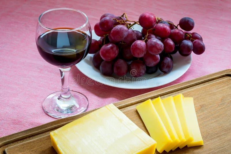 Primer del vidrio de vino tinto, de queso Edam amarillo cortado del queso en tabla de cortar de madera marrón y de uvas rojas dul foto de archivo libre de regalías