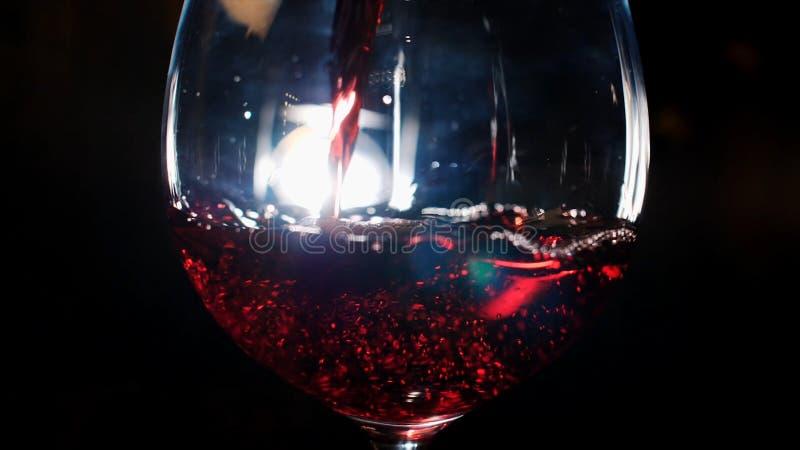Primer del vidrio que vierte con el vino espumoso rojo en la oscuridad con la luz blanca en el fondo Cantidad com?n Vista a imágenes de archivo libres de regalías
