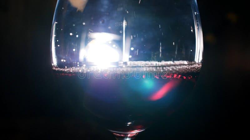 Primer del vidrio que vierte con el vino espumoso rojo en la oscuridad con la luz blanca en el fondo Cantidad com?n Vista a imagen de archivo