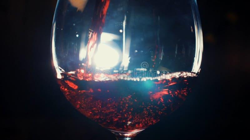 Primer del vidrio que vierte con el vino espumoso rojo en la oscuridad con la luz blanca en el fondo Cantidad com?n Vista a fotos de archivo libres de regalías