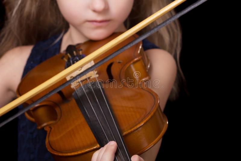 Primer del violín de la muchacha que toca el violín aislado en fondo negro imagen de archivo libre de regalías