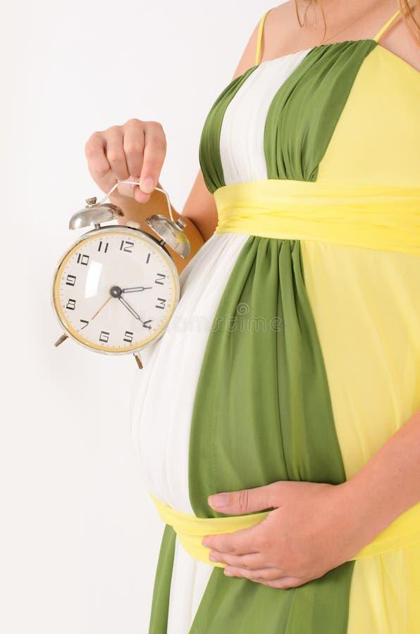 primer del woman& embarazada x27; vientre y reloj de s fotos de archivo