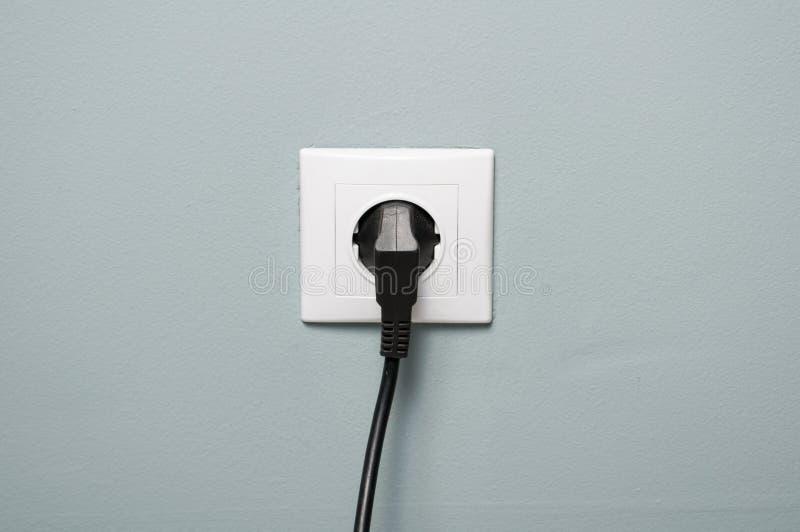Primer del zócalo eléctrico con el cable negro enchufado imagenes de archivo