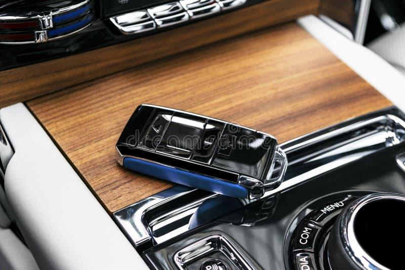 Primer dentro del vehículo de la ignición dominante de cuero azul inalámbrica en el panel de madera natural Llave inalámbrica del fotos de archivo