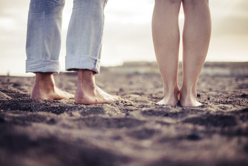Primer descalzo dos pares de retrato caucásico de los pies en la playa visto de detrás, amor y el concepto íntimo para joven fotos de archivo libres de regalías