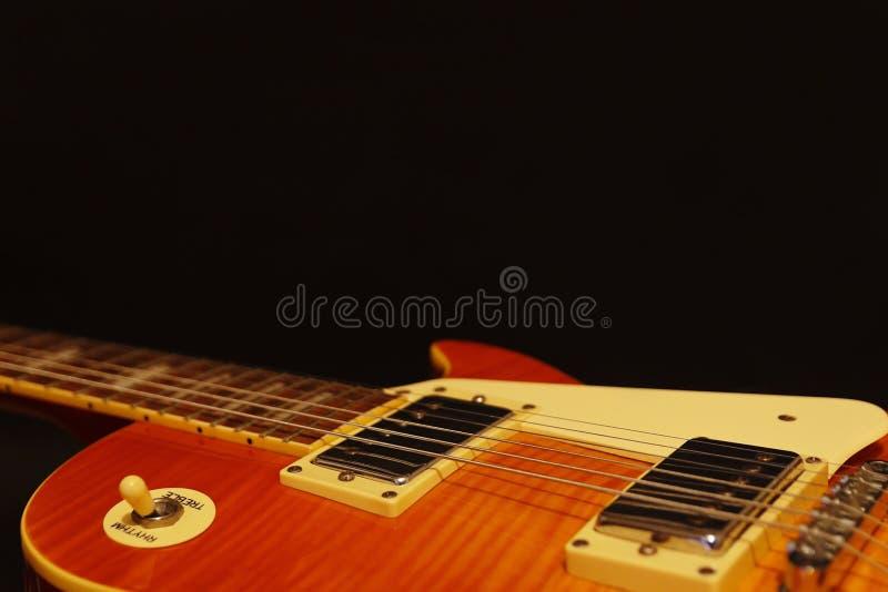 Primer eléctrico de la guitarra del jazz del vintage del resplandor solar de la miel en fondo negro, con el un montón de espacio  imagen de archivo