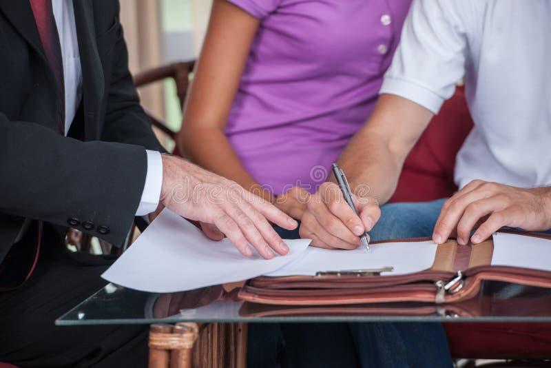 Primer en el acuerdo de firma de la mano feliz del hombre en nueva casa fotografía de archivo libre de regalías