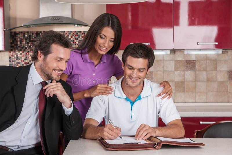 Primer en el acuerdo de firma del hombre feliz en nueva casa foto de archivo libre de regalías