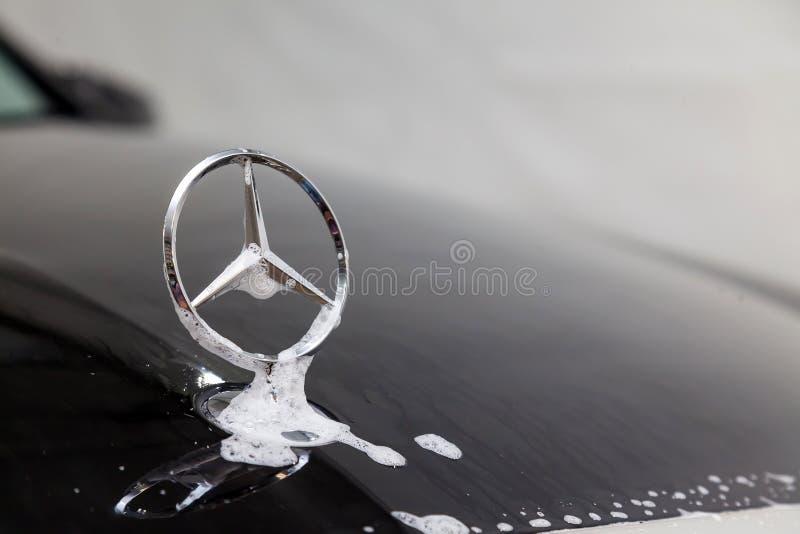 Primer en el emblema de un fabricante de automóviles Mercedes Benz en la capilla de un coche negro durante lavarse y la limpieza  imagenes de archivo