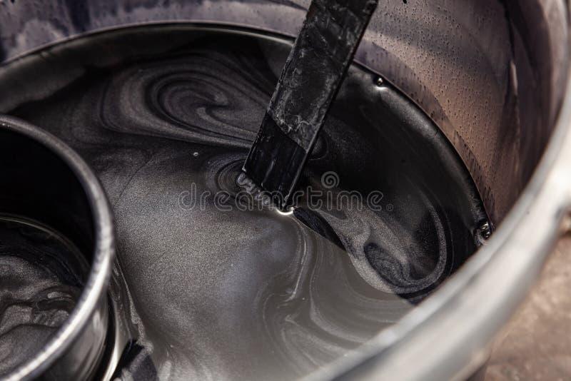 Primer en el tanque con la pintura negra de plata mientras que se mezcla con los modelos espirales en la pintura foto de archivo libre de regalías