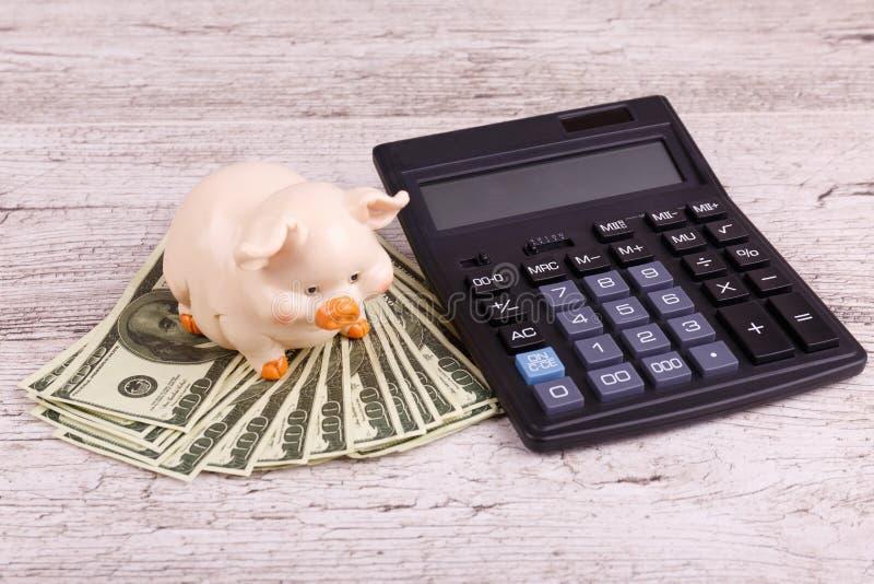 Primer en fondo, la hucha y la calculadora grises del dinero fotos de archivo libres de regalías